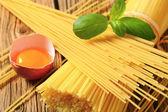 Dried spaghetti and raw egg — Stock Photo