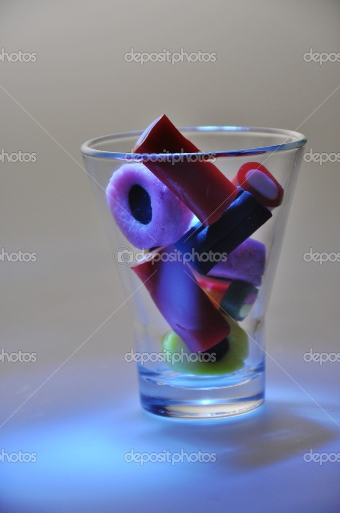 Colored candy in a glass, blue illumination — Stock Photo #13902405