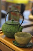 Iron asian teapot with sprigs of mint for tea — Stockfoto