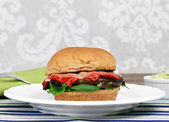 Portobello mushroom burger on a whole wheat bun with roasted pep — Stock Photo