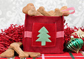 Homemade dog cookies in a decorative Christmas bag. — Stock Photo