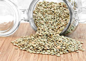 Healthy green lentil beans spilling from a jar.  Selective focus — Stock Photo