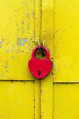 Red lock on a rusty yellow door — Stock Photo