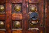 An old door with circle iron door-handle — Stock Photo