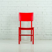 Red wooden chair in empty white room against a brick wall — Stock Photo