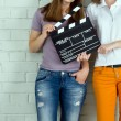 Two young girls holding a clapboard against brick wall with copy — Stock Photo