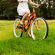 Woman riding in the park. Wheel in motion blur — Stock Photo