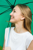 Happy smiling girl holding a green umbrella — Stock fotografie