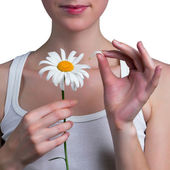 Young girl guesses on a chamomile flower — Stock Photo