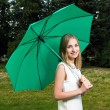 Beautiful smiling girl holding a green umbrella in a park — Stock Photo