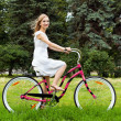 Stock Photo: Young happy girl riding pink bicycle in park