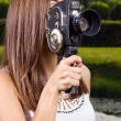 Young girl using an old fashioned cinema camera in a park — Stock fotografie