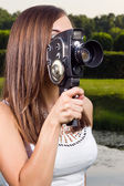 Young girl using an old fashioned cinema camera in a park — Stock Photo