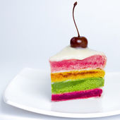 A colorful cake decorated with a cherry on the top — Stock Photo