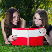 Two young happy smiling girls reading an open book — Stock Photo