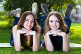 Happy smiling young women lying on grass — Стоковое фото