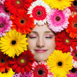 Happy beautiful girl with flowers around her face — Stock Photo