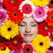 Happy beautiful girl with flowers around her face — Stock fotografie