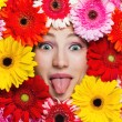 Happy girl sticking out tongue. Beautiful girl with gerbera — Stockfoto