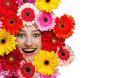 Happy smiling girl with flowers around face isolated on white — Stock Photo
