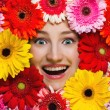 Happy smiling girl with flowers around her face. Gerbera daisy f — Stockfoto