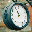 Stock Photo: Vintage street clock. 5 minutes to twelve concept