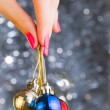 Womhand holding Christmas balls over bekeh background with co — Stock Photo #37744957