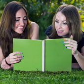 Two young girls reading a book — Stock Photo