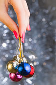 Woman hand holding Christmas balls over bekeh background with co — Stok fotoğraf