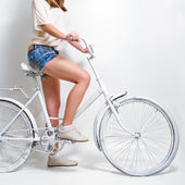 Young woman riding a white vintage bicycle — Stock Photo