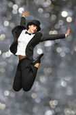Woman wearing retro suit and top hat jumping — Stock Photo
