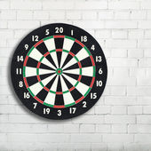 Darts board on a white brick wall with copy space — Stock Photo