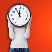 Woman holding clock over face — Stock Photo