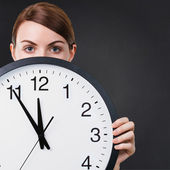 Young woman holding a big clock — Stock Photo