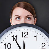 Woman face with a big clock — Stock Photo