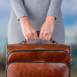Woman holds leather suitcase — Stock Photo #48598437