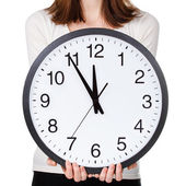 Woman holding office clock — Stock Photo