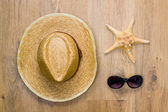 Braided hat, sea star and glasses — Stock Photo