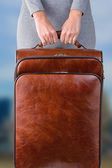 Woman holds leather suitcase — Stock Photo