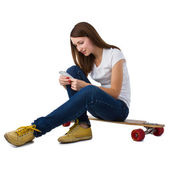 Woman sitting on skateboard with smart phone — Stock Photo
