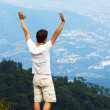 Young man standing on a cliff side — Stock Photo #50210897