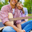Cheerful teenage couple with guitar in park — Stock Photo