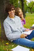 Happy students studying into autumn park — Stok fotoğraf