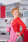 Beautiful young housewife in kitchen holding ladle — Stock Photo