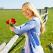Pretty girl with flowers in country — Stock Photo