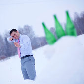 Businessman in winter forest with slingshot — Stock Photo