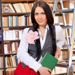 Stock Photo: Pretty student with book in library