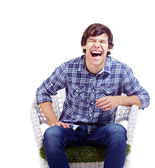 Laughing guy in armchair — Stock Photo