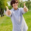 Happy guy showing thumbs up in park — Stock Photo