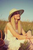 Young girl in straw hat sitting in field — Stock Photo